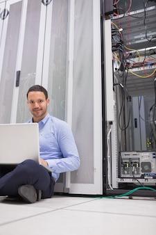 Homme assis sur le sol en utilisant un ordinateur portable pour vérifier les serveurs