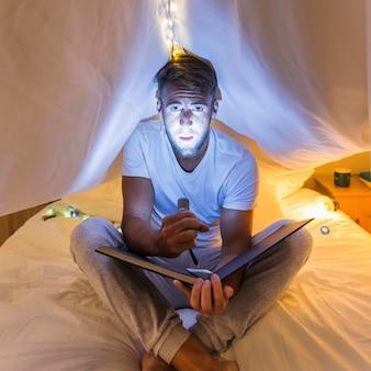 Homme assis sous le rideau sur le lit, tenant l'album met en évidence son visage avec une lampe de poche