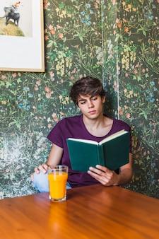 Homme assis à table et livre de lecture