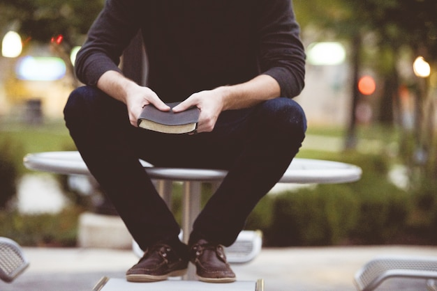 Homme assis sur une table de parc et tenant la bible
