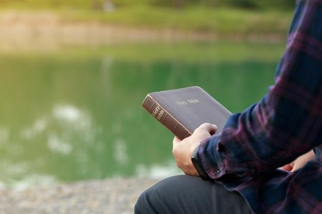 Homme assis et tenant la bible dans ses mains avec un fond de nature. lectures du dimanche, bible