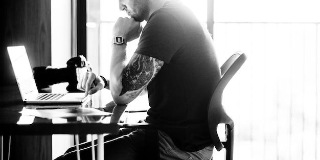 Homme assis travaillant sur un ordinateur portable en niveaux de gris