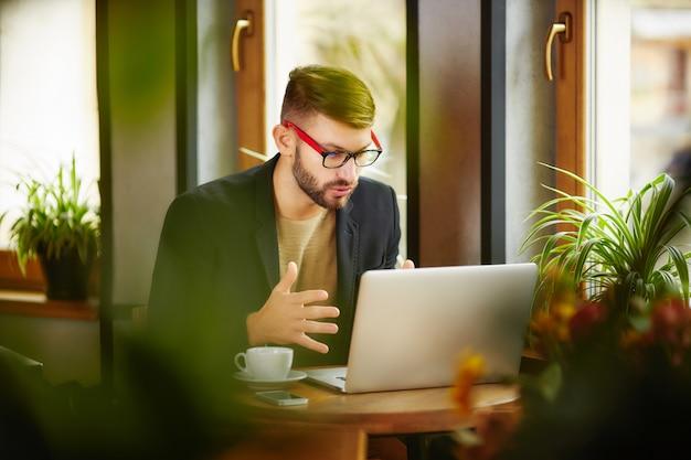 Homme assis et travaillant à l'ordinateur portable