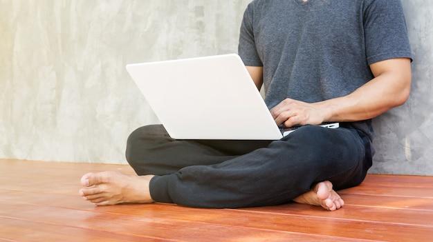 Homme assis et utilise un ordinateur portable blanc.
