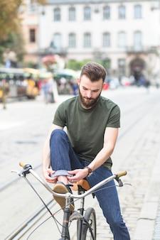 Homme assis sur un vélo en pliant ses jeans