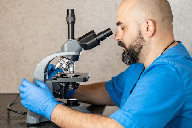 Homme assistant de laboratoire examinant des échantillons de biomatériaux dans un microscope