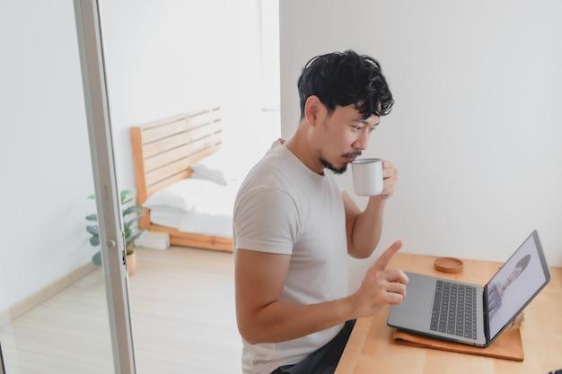 L'homme assiste à une conférence de réunion avec son collègue pendant qu'il travaille à domicile