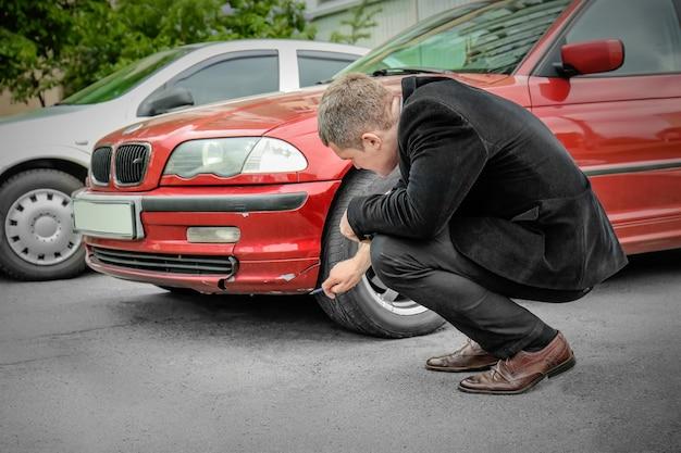 L'homme d'assurance vérifiant la voiture cassée après un accident