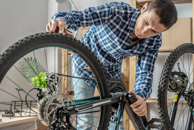 Un homme de l'atelier démonte son vélo et le répare. concept d'entretien et de préparation pour la nouvelle saison