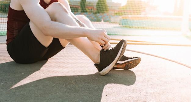 Homme athlète assis attachant des lacets