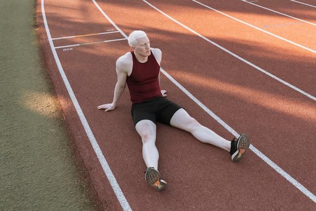 Homme athlète assis sur une piste de course