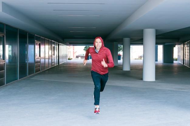 Homme d'athlète de confiance en sweat à capuche courir sous terre