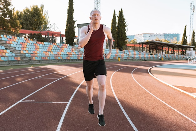 Homme athlète qui court sur une piste de course