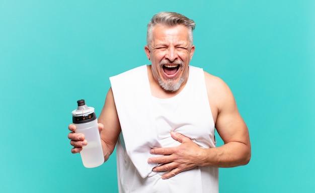 Homme athlète senior riant aux éclats d'une blague hilarante, se sentant heureux et joyeux, s'amusant