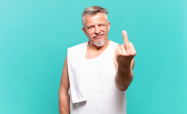 Homme athlète senior se sentant en colère, agacé, rebelle et agressif, renversant le majeur, ripostant