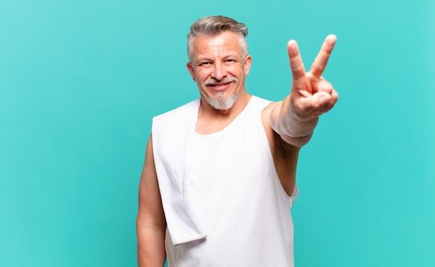 Homme athlète senior souriant et ayant l'air heureux, insouciant et positif, gesticulant la victoire ou la paix d'une main