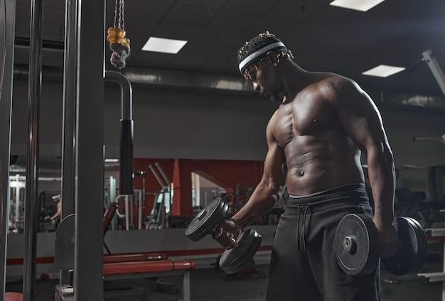 Homme athlétique afro-américain faisant de l'exercice avec des haltères en formation de gym perdre du poids et en bonne santé