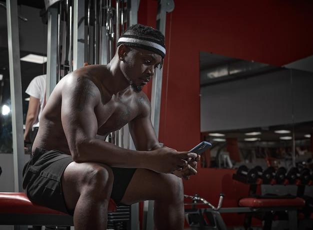 Un homme athlétique afro-américain avec un téléphone utilisant une application sportive pour faire de l'exercice en salle de sport et