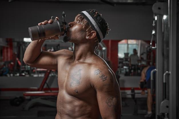 Homme athlétique afro-américain avec torse nu, eau potable ou nutrition sportive en verre après