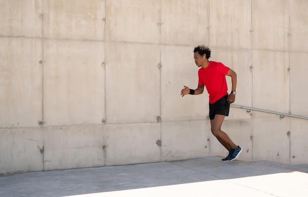 Homme athlétique afro en cours d'exécution et faire de l'exercice à l'extérieur dans la rue