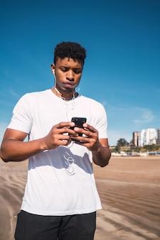 Homme athlétique à l'aide de son téléphone portable.
