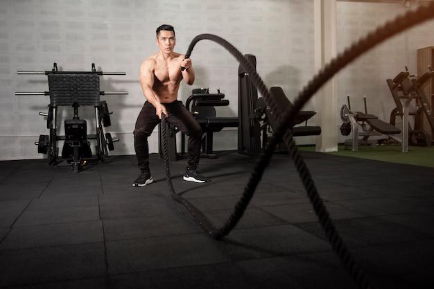Homme athlétique asiatique avec corde faisant de l'exercice dans la salle de fitness