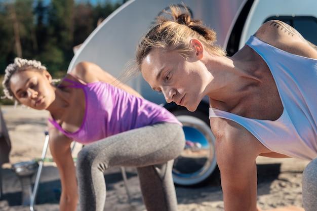 Homme athlétique. athlétique bel homme aux cheveux blonds faisant du yoga avec sa petite amie attrayante