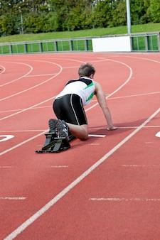Homme athlétique en attente dans le bloc de départ