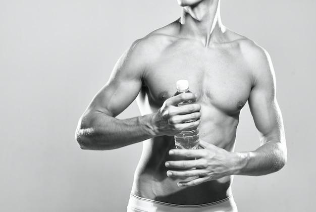 Homme athlétique bouteille d'eau corps musclé studio posant