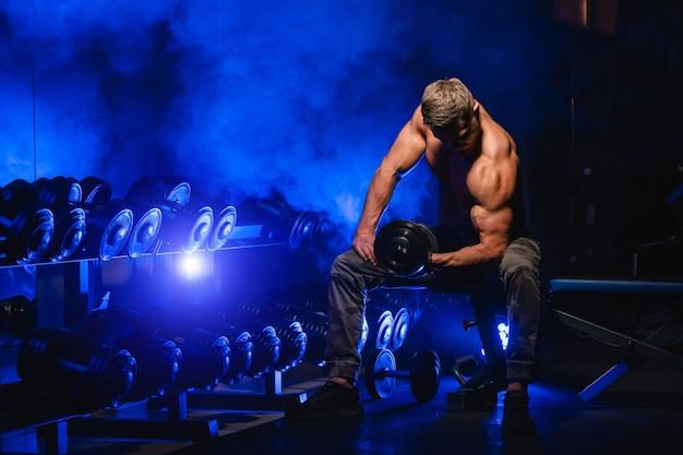 Homme athlétique dans la salle de gym s'exerçant sur le développé couché avec haltères. bodybuilder avec un corps parfait. filtre bleu. vue depuis le sommet. torse nu.