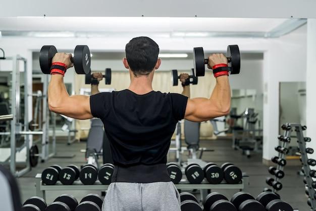 Homme athlétique dans une salle de sport travaillant avec des haltères
