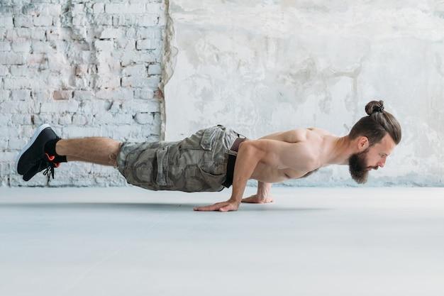 Homme athlétique d'endurance de force d'exercice statique