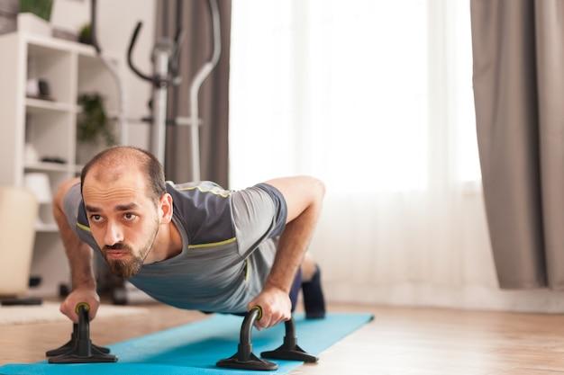 Homme athlétique faisant des pompes sur un tapis de yoga pendant l'auto-isolement de covid-19.