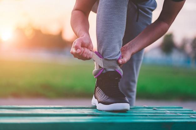 Homme athlétique met des poids sportifs pour marcher pendant l'entraînement en plein air. mode de vie sain et sportif.