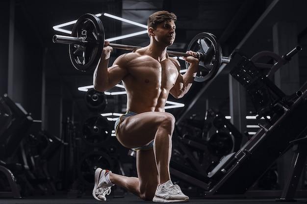 Homme athlétique pompant en faisant des exercices de fentes dans une salle de sport. pompage des muscles des jambes avec haltères, concept de remise en forme et de sport