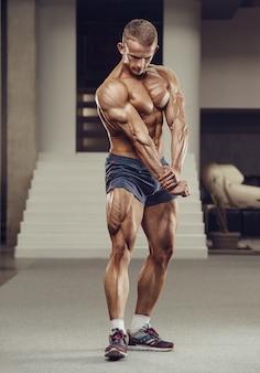 Homme athlétique de puissance caucasienne, formation de pompage des muscles quadriceps de la jambe. bodybuilder fort avec six pack, abs parfaits, triceps, poitrine, épaules dans la salle de gym. concept de remise en forme et de musculation