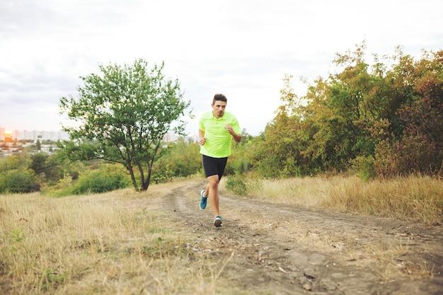 Homme athlétique qui court dans le parc