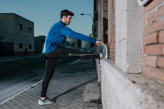 Homme athlétique s'échauffant sur la rue