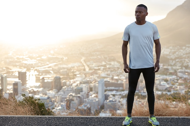 Homme athlétique sain et réfléchi avec un corps en forme, se dresse sur une colline contre une vue sur la ville, porte des vêtements décontractés, un espace libre sur le côté gauche pour votre contenu publicitaire. concept de personnes, de motivation et d'énergie