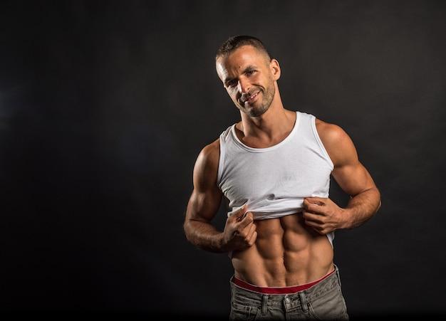 Homme athlétique soulevant sa chemise pour montrer ses abdos. coup moyen. fond noir.
