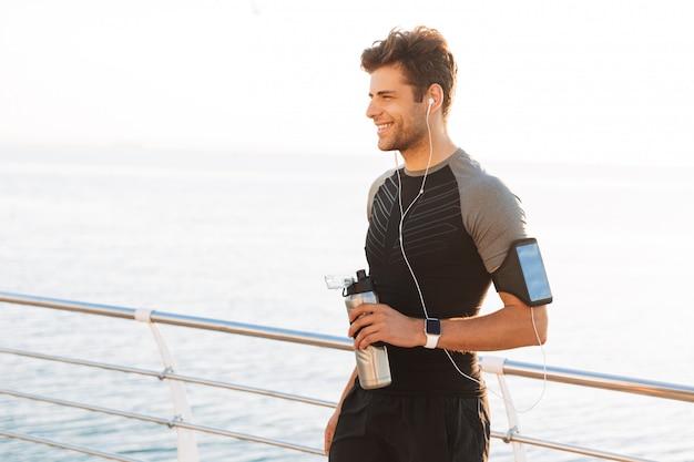 Homme athlétique en t-shirt écoutant de la musique via des écouteurs sans fil et tenant une tasse en métal avec de l'eau, pendant une promenade en plein air au bord de la mer