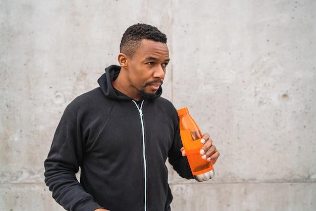 Homme athlétique tenant une bouteille d'eau.