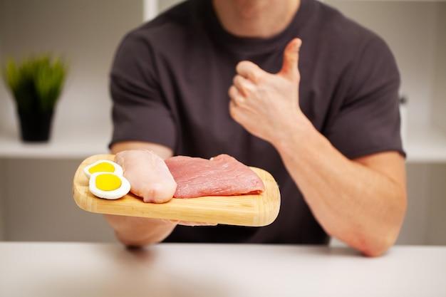 Homme athlétique tenant une planche avec de la viande pour une bonne nutrition de l'athlète