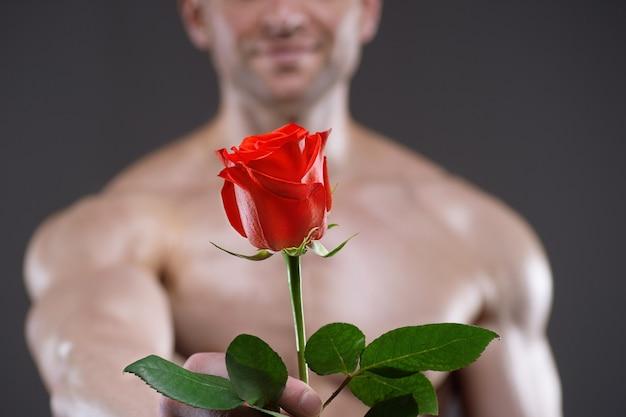 Homme athlétique tenant une rose rouge à la main. concept de relations amoureuses et romantiques