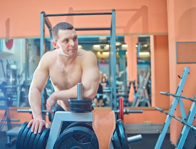 Homme athlétique avec torse nu posant dans une salle de sport