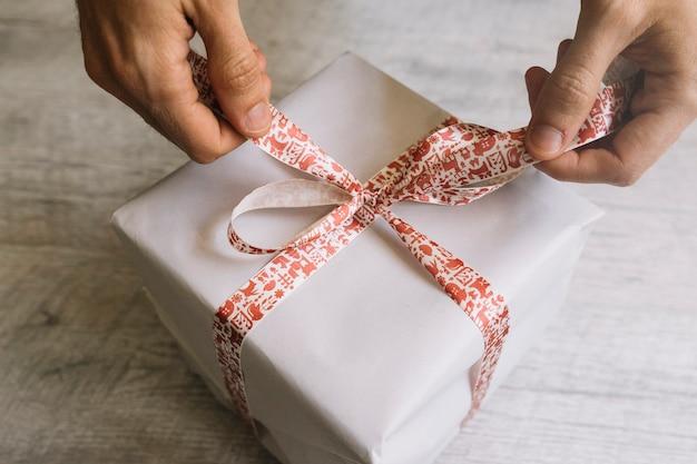 Homme attachant un arc sur une boîte cadeau blanche