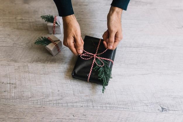 Homme attachant un arc sur une boîte cadeau noire