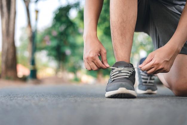 Homme attachant des chaussures de course sur le parc