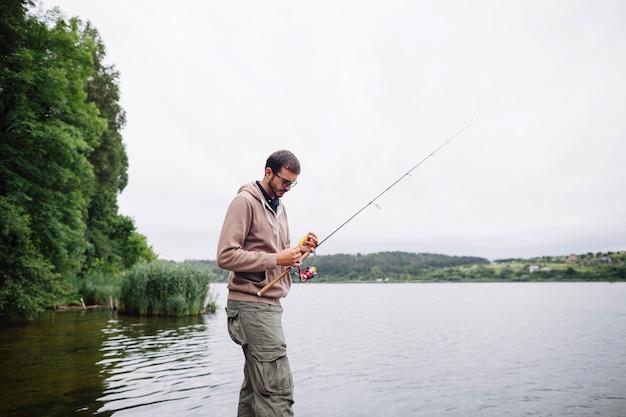 Homme attachant leurre de pêche sur la tige près du lac