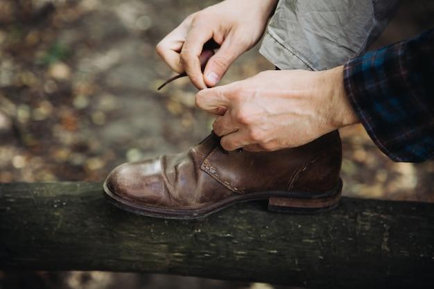 Homme attachant ses chaussures en cuir dans les bois